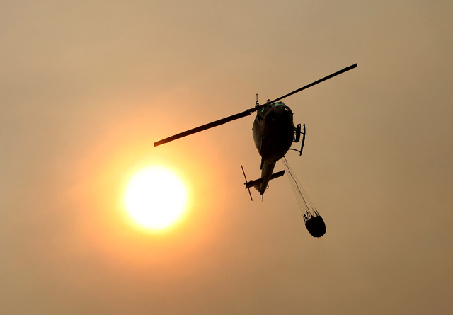 A Cal Fire helicopter flies over Pfeiffer Ridge on Monday, Dec. 16, 2013, in Big Sur, Calif. The wildfire burning Monday in the Big Sur area of California destroyed at least 15 homes and forced ab ...