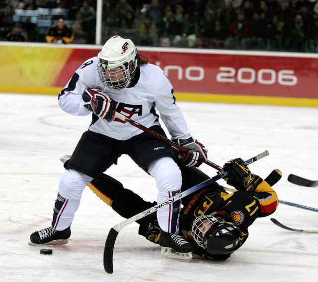 In this Feb. 12, 2006, file photo, the United States' Caitlin Cahow (8) upends Germany's Sara Seiler during the first period of a 2006 Winter Olympics ice hockey match in Turin, Italy. Cahow will  ...