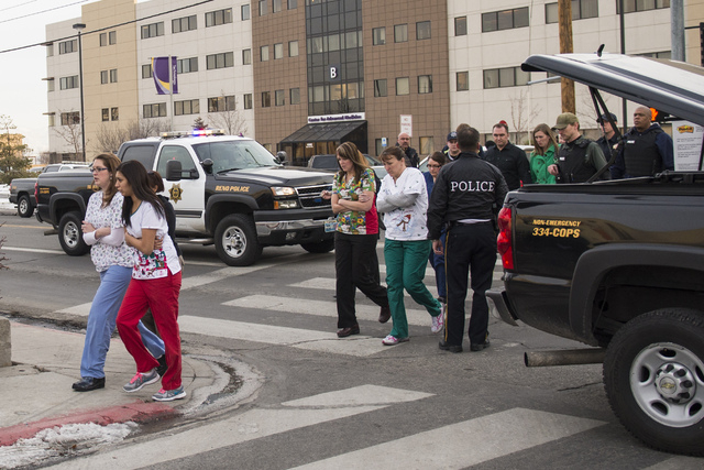 Officers escort witnesses to a bus at the Renown Regional Medical Center in Reno on Tuesday after a lone gunman shot and killed one person and injured two others before killing himself. (AP Photo/ ...