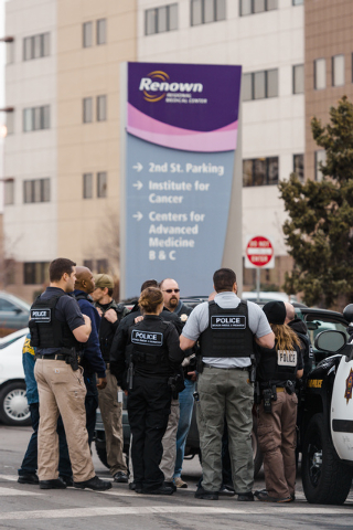 Officers gather in front of the Renown Regional Medical Center in Reno on Tuesday after a lone gunman shot and killed one person and injured two others before killing himself. (AP Photo/Scott Sady)