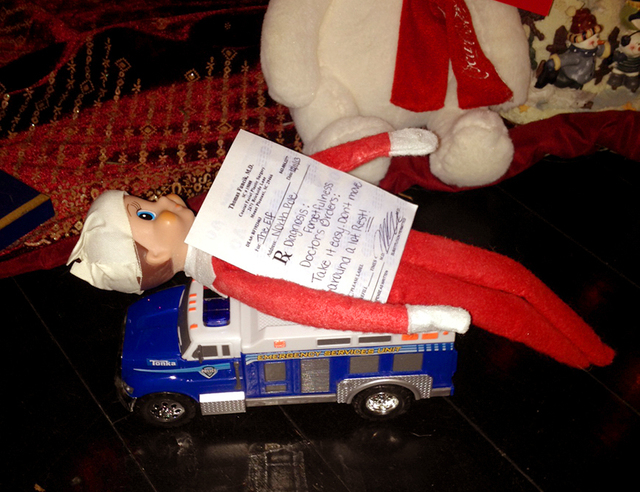 """A bandaged elf from """"The Elf on the Shelf"""" lies with a prescription by the Christmas tree in the Kim Boerman home in Charleston, S.C. Boerman procured a doctor's prescription after the elf fell fr ..."""