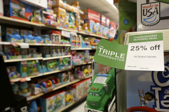 """In this Nov. 28 photo, a """"Triple Doorbuster"""" sale sign is placed at the toys section in Kmart during Grey Thursday shopping in New York. Consumer spending rose in November by the most in five mont ..."""