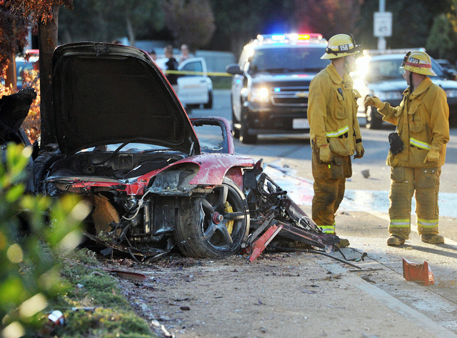 In this Nov. 30, 2013 file photo, firefighters stand near the wreckage of a Porsche that hit a light pole and burned on Hercules Street near Kelly Johnson Parkway in Valencia, Calif., a crash that ...