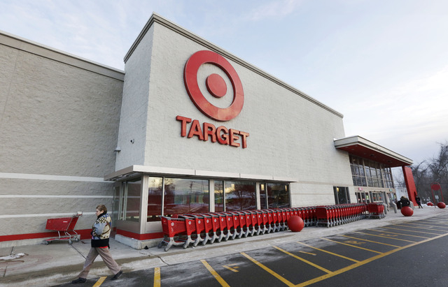 A passer-by walks near an entrance to a Target retail store on Thursday in Watertown, Mass. Target says that about 40 million credit and debit card accounts may have been affected by a data breach ...
