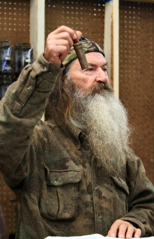 "Phil Robertson, the Duck Commander, holds the 1 millionth duck call assembled for 2013 at the company's warehouse in West Monroe, La. The A&E channel says ""Duck Dynasty"" patriarch Robertson is off ..."