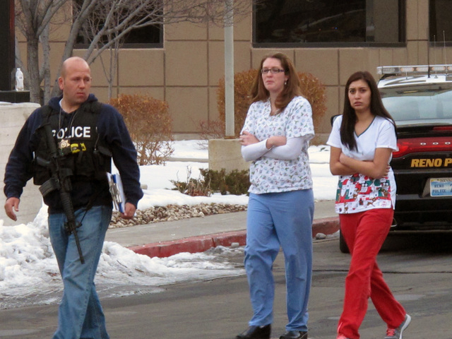 Police escort hospital staff away from a medical office building in Reno, Nev., on Tuesday, Dec. 17, 2013. A suicidal gunman killed one person and critically wounded two others before turning the  ...