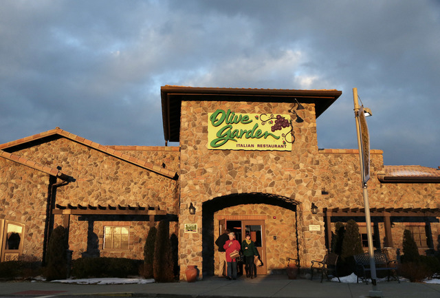 In this Wednesday, March 20, 2013 file photo, people leave an Olive Garden restaurant at sunset in Foxborough, Mass. Darden Restaurants Inc. reports quarterly financial results before the market o ...
