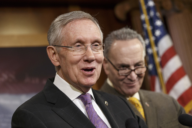 Senate Majority Leader Harry Reid, D-Nev., joined at right by Sen. Chuck Schumer, D-N.Y.,  talks to reporters at the Capitol in Washington, Thursday, Dec. 19, 2013. (AP Photo/J. Scott Applewhite)