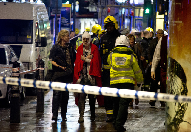 A woman stands bandaged and wearing a blanket  given by emergency services  following an incident at the Apollo Theatre, in London's Shaftesbury Avenue, Thursday evening, Dec. 19, 2013, during a p ...