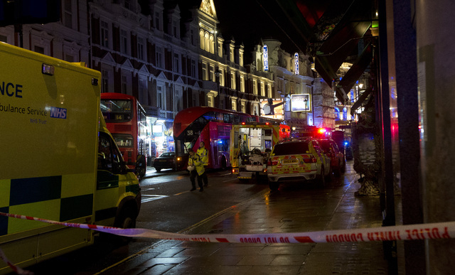 Emergency service vehicles gathered among London buses  following an incident  during a performance at the Apollo Theatre, far right, in London's Shaftesbury Avenue, Thursday evening, Dec. 19, 201 ...