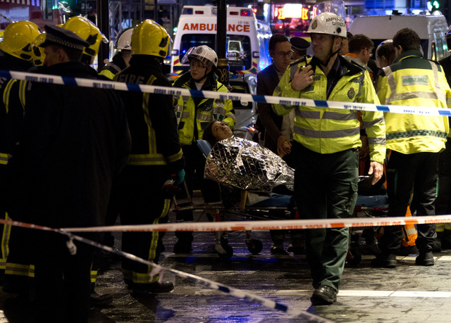 A woman lies on a stretcher surrounded  by rescue workers, awaiting evacuation  following an incident during a performance at the Apollo Theatre, in London's Shaftesbury Avenue, Thursday evening,  ...