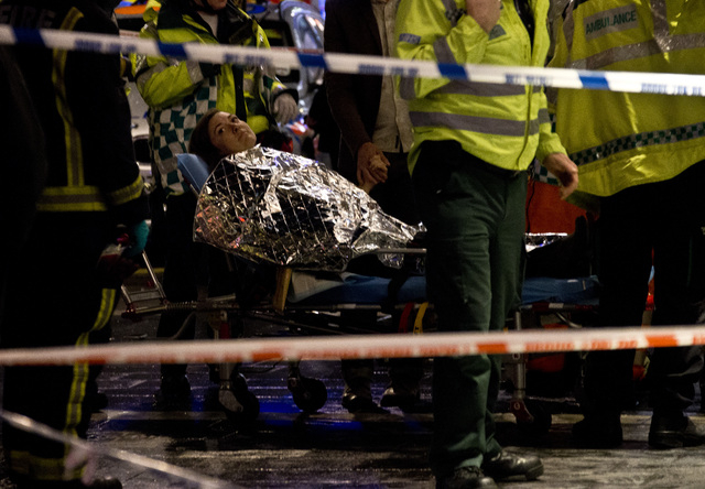 An injured woman is moved on a stretcher following an incident at the Apollo Theatre, in London's Shaftesbury Avenue, Thursday evening, Dec. 19, 2013 during a performance , with police saying ther ...