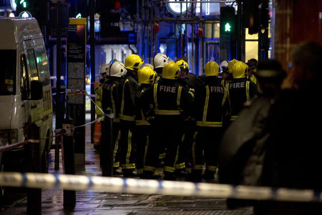 Firemen confer at the scene following an incident at the Apollo Theatre, in London's Shaftesbury Avenue, Thursday evening, Dec. 19, 2013, during a performance at the height of the Christmas season ...