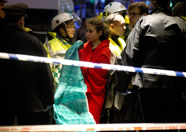 A girl wraps herself in a blanket provided by rescue services following an incident during a performance at the Apollo Theatre, in London's Shaftesbury Avenue, Thursday evening, Dec. 19, 2013  , w ...