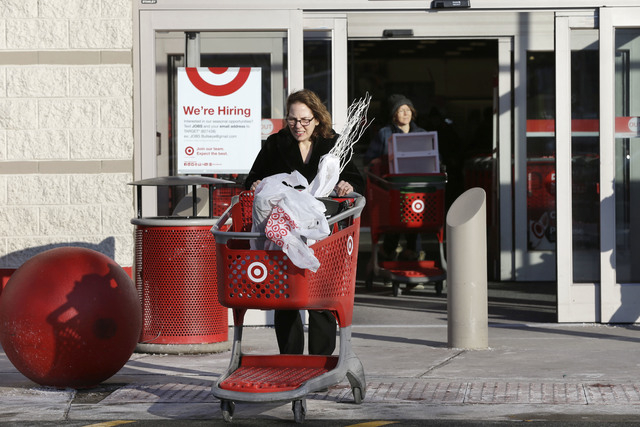 Customers push shopping carts as they depart a Target retail store Thursday, Dec. 19, 2013 in Watertown, Mass. Target says that about 40 million credit and debit card accounts may have been affect ...