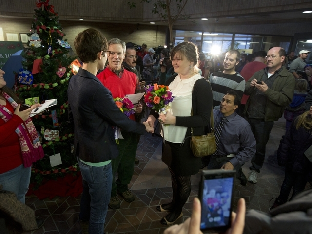 Natalie Dicou, left, and Nicole Christensen, right, are married by Salt Lake City Mayor Ralph Becker, middle, in the lobby of the Salt Lake County Clerk's Office in Salt Lake City on Friday, Dec.  ...
