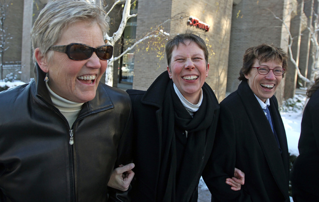 In this Dec. 4, 2013 file photo, plaintiffs Laurie Wood, left, and her partner, Kody Partridge, center, walk with their attorney Peggy Tomsic after leaving the Frank E. Moss United States Courthou ...