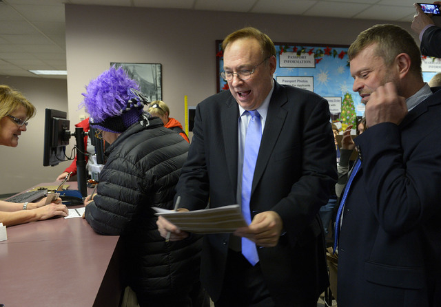 Utah State Sen. Jim Dabakis, second from right, deals with the paperwork of a marriage license as his partner, Stephen Justesen waits at right as others also see the clerks at the marriage license ...