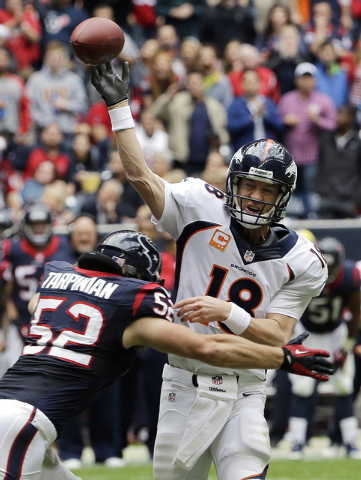 Denver Broncos' Peyton Manning (18) is pressured by Houston Texans' Jeff Tarpinian (52) during the second quarter of an NFL football game on Sunday, Dec. 22, 2013, in Houston. (AP Photo/David J. P ...