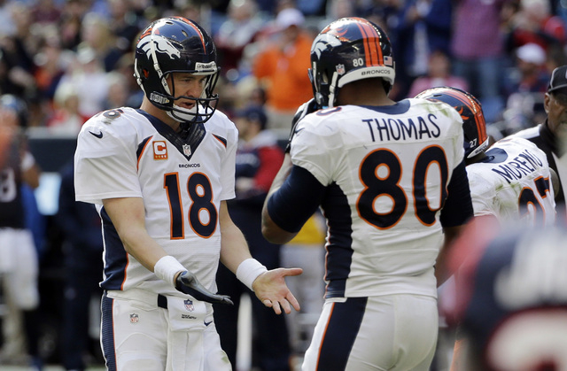 Denver Broncos' Peyton Manning (18) celebrates with Julius Thomas (80) and other teammates after throwing a pass for a touchdown against the Houston Texans during the third quarter of an NFL footb ...