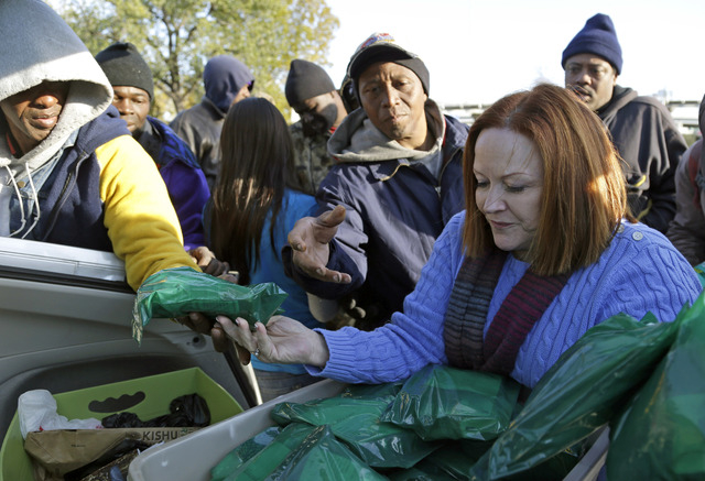 In this Dec. 10, 2013 photo, Jacquie Brennan, right, of A Simple Thread, hands out support kits to a group of homeless people in Houston. Brennan's volunteer group received a large donation from T ...