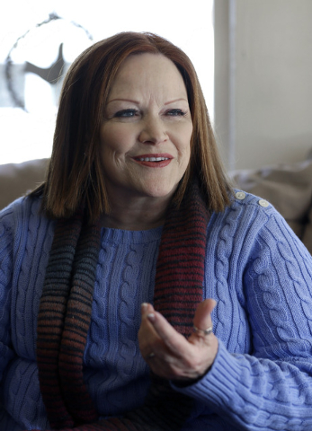 In this Dec. 10, 2013 photo, Jacquie Brennan, founder of A Simple Thread, talks in her home about their volunteer work and the donations they received from The Original OKRA Charity Saloon, in Hou ...