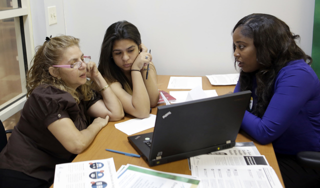 In this Friday, Dec 20, 2013 photo, certified enrollment specialist Richelle Baker, right, talks to Martha Medina, left, and her daughter Martha, both from Hialeah, Fla., at a Healthcare Insurance ...