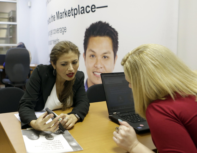 In this Friday, Dec 20, 2013 photo, in Johanna Diaz, left, points out information to Senior Certified Enrollment Specialist Marlene Nesmith at a Healthcare Marketplace office in Miami. Diaz, who h ...