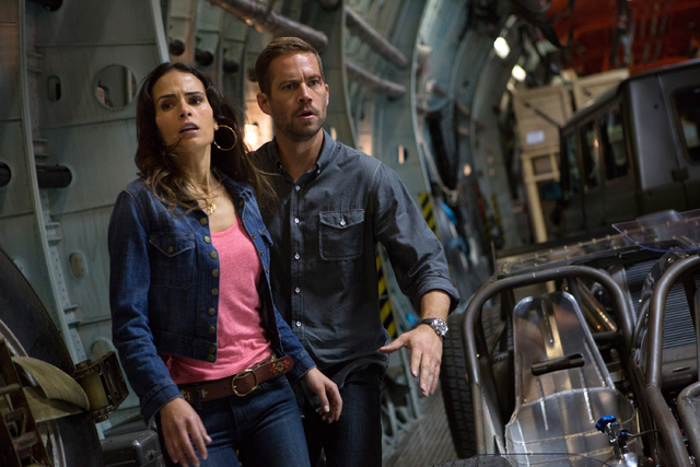 "This film publicity image released by Universal Pictures shows Jordana Brewster, left, and Paul Walker in a scene from ""Fast & Furious 6."" Universal Pictures has delayed the release of F ..."