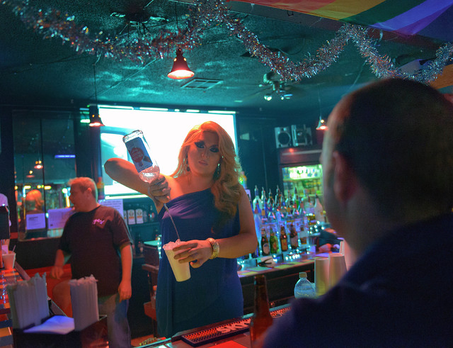 This Saturday, Dec. 21, 2013 photo shows Jordan Williams, who goes by the stage name Tanzi Taylor, mixing a drink at Club Pink, a bar for Lesbian Gay Bisexual and Transexual customers owned by Tom ...