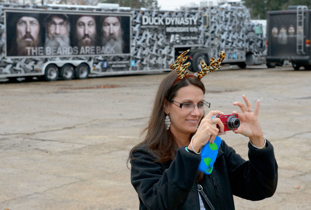 """This Dec. 21, 2013 photo shows Trish Singlteon, of Durant, Okla., taking a picture of her family outside the Duck Commander store in West Monroe, La. The town is the setting for the popular """" ..."""