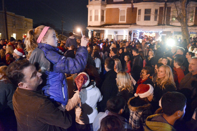 Mike Simmons holds his daughter Gracie Simmons, 11, both of Wyomissing, while Gracie shoots video of the caroling, Saturday, Dec. 21, 2013, in West Reading, Pa., where thousands of people came out ...