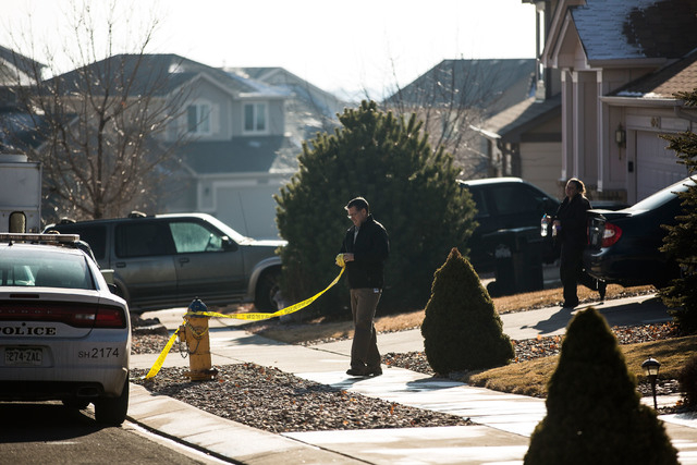 Colorado Springs Police officers take down caution tape outside of a house where a 14-year-old girl was mistakenly shot by her stepfather Monday, Dec. 23, 2013 at their home in northeast Colorado  ...