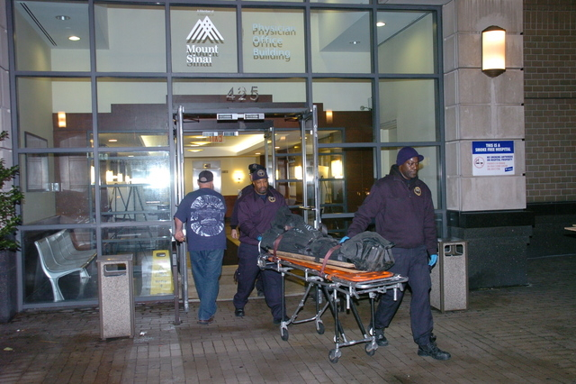 The body of Dmitriy Kanarikov, 35, is removed from 425 west 59th street, Sunday, Dec. 22, 2013, in New York. Authorities said they received an emergency call reporting two jumpers from the buildin ...