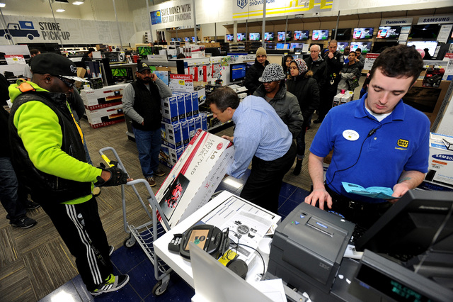 FILE - In this Nov. 29, 2013, file photo, Best Buy employee Christopher Gervais, right, rings up a 32-inch LED TV in Dunwoody, Ga.  Sales at U.S. stores dropped 3.1 percent to $42.7 billion for th ...