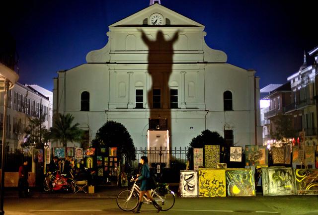 FILE - In this Friday, Feb. 1, 2013 file photo, a pedestrian walks her bicycle past a silhouette of Jesus Christ projected against the Cathedral-Basilica of Saint Louis King of France in New Orlea ...