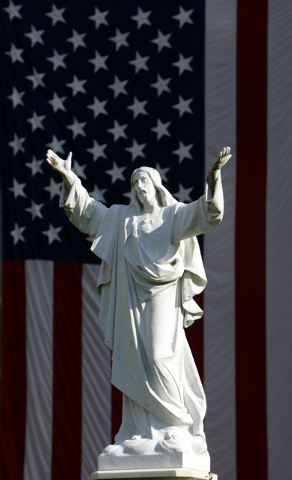 FILE - In this Sunday, Oct.  9, 2005 file photo, a large American flag hangs at the Loyola University campus in New Orleans behind a life-size statue of Jesus Christ. In America, white Jesus image ...