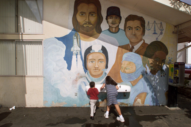 FILE - In this Sunday, Sept. 29, 2002 file photo, children drink from a water fountain below a mural on an annex building of the Church of the Guardian Angel in the Pacoima neighborhood of Los Ang ...