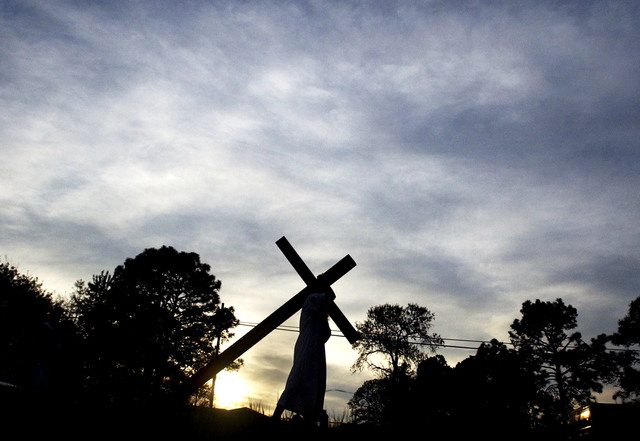 FILE - In this April 14, 2006 file photo, Christopher Riddle portrays Jesus Christ as he carries a cross down Highway 210 in Spring Lake, N.C., on his way to Full Gospel Zion Church during the sev ...