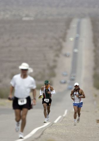 In this July 23, 2007 file photo, Jorge Pacheco, center, of Mexico, runs in Kiehl's Badwater Ultramarathon in Death Valley, Calif. The race start line wa at Badwater, Death Valley, which marks the ...