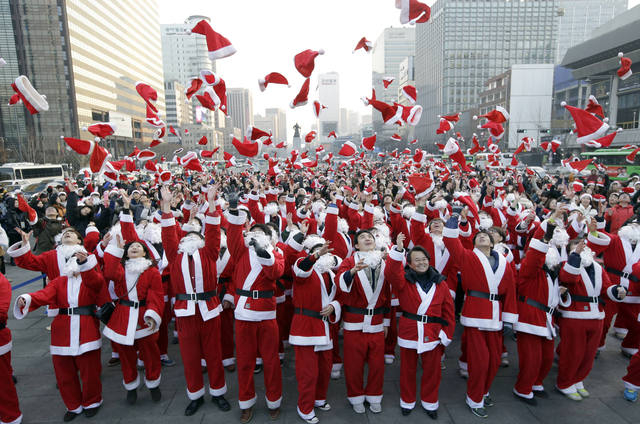 more than 1000 volunteers clad in santa claus costumes throw their hats in the air as