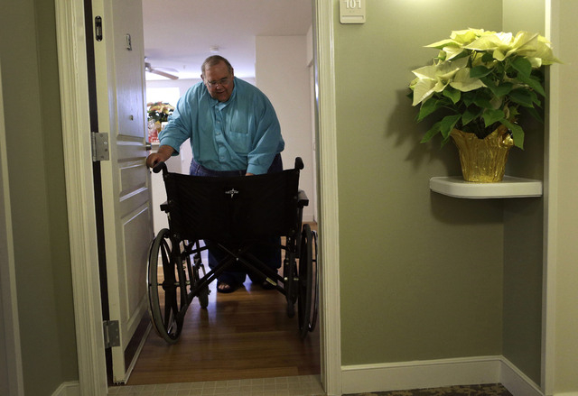 In this Dec. 21, 2013 photo, George Warren pulls his wheelchair through his apartment's front door at Village Crossroads, an affordable senior community in Nottingham, Md. Warren's wheelchair is t ...