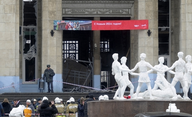 A police officer guards a main entrance to the Volgograd railway station hit by an explosion, in Volgograd, Russia,  Sunday, Dec. 29, 2013. More then a dozen people were killed and scores were wou ...