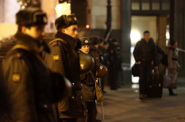 Police officers guard the Volgograd main railway station as passengers from arriving trains leave, in Volgograd, Russia, early Monday. A bomb blast tore through a city trolleybus in Volgograd on M ...