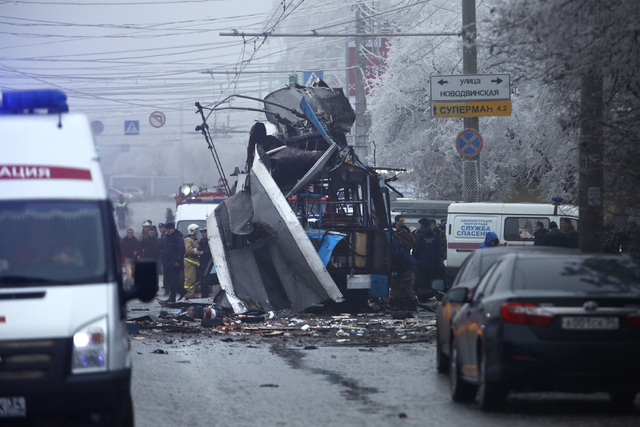 Experts and police officers examine a site of a trolleybus explosion in Volgograd, Russia, on Monday. A bomb blast tore through the trolleybus, killing at least 14 people a day after a suicide bom ...