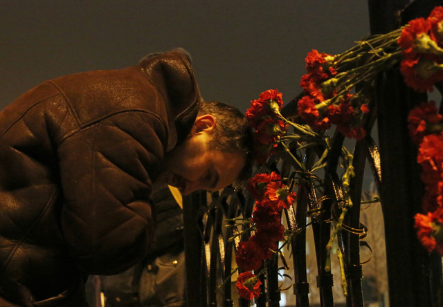 A  man grieves outside the Volgograd main railway station in Volgograd, Russia, early Monday. A bomb blast tore through a trolleybus in the city of Volgograd on Monday morning, killing at least 14 ...