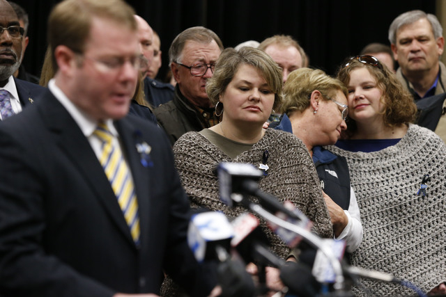 Stauffer Presser, center, reacts on Sunday in Tupelo, Miss., as FBI Special Agent in Charge Danile McMullen announces they believe the bank robber who killed her husband, Sgt. Gale Stuaffer on Mon ...