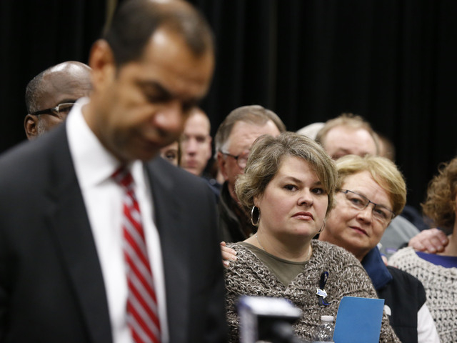 Beth Stauffer, center, reacts on Sunday in Tupelo, Miss., as FBI Special Agent in Charge Danile McMullen announces they believe the bank robber who killed her husband, Sgt. Gale Stuaffer on Monday ...