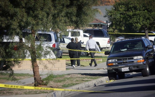 Police crime scene investigators arrive Tuesday at a home in Fontana, Calif., where a family of four were found shot to death Monday night. (AP Photo/The Press-Enterprise, Kurt Miller)