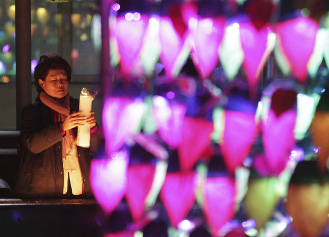 A Buddhist woman holding a candle light prays ahead of the new year at Chogye Buddhist temple in Seoul, South Korea, on Tuesday. (AP Photo/Ahn Young-joon)